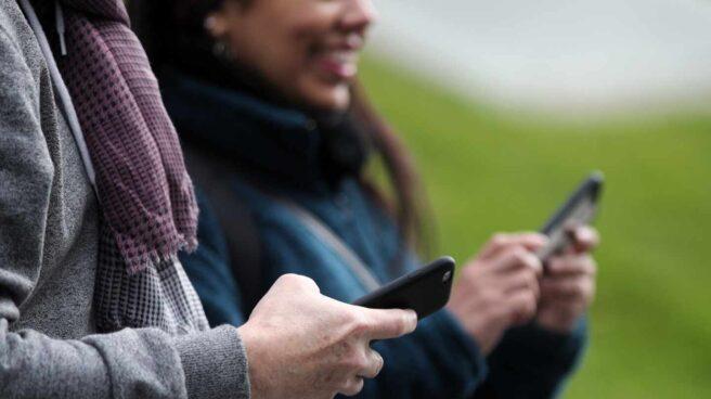 Dos paseantes utilizando su teléfono móvil.