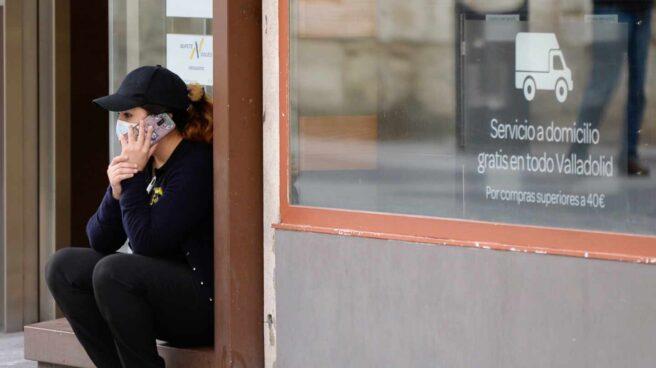 Una trabajadora llama desde la puerta de un supermercado.