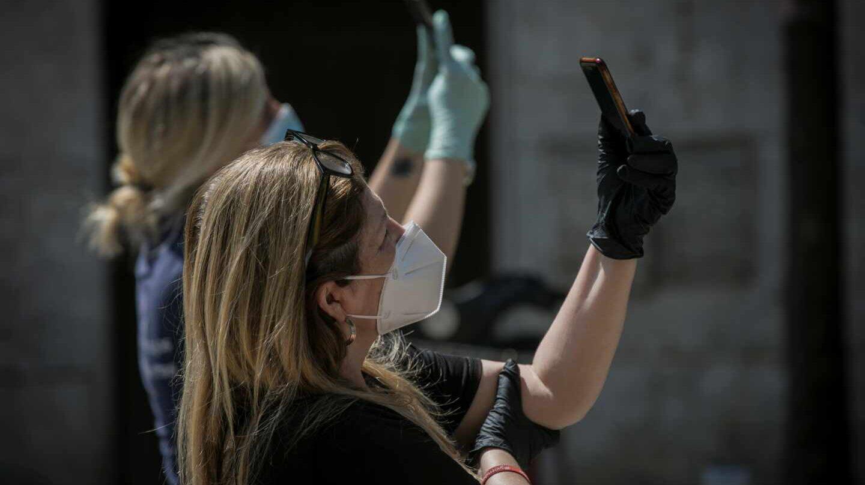 Ciudadanas con mascarilla utilizando sus móviles.