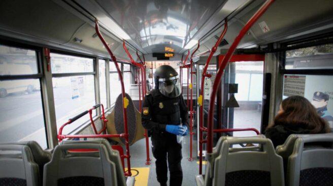 Un policía reparte mascarillas a los pasajeros de un autobús en A Coruña.