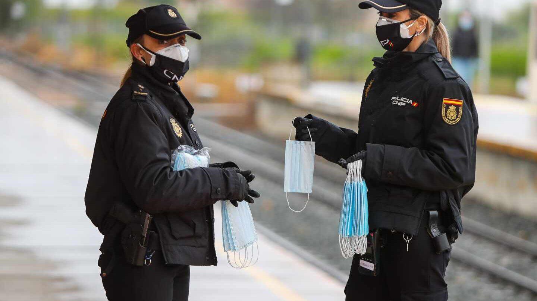Policías nacionales, repartiendo mascarillas en una estación de tren.
