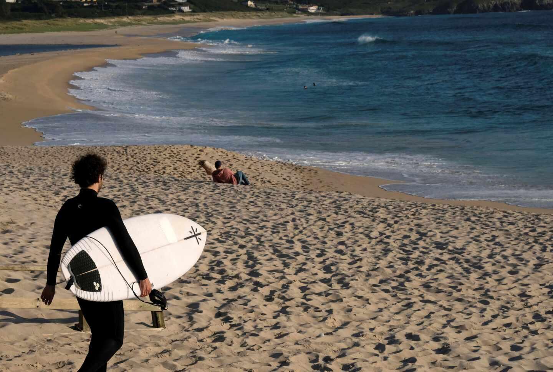Un hombre con una tabla de surf este lunes en los arenales próximos a Ferrol (Galicia).