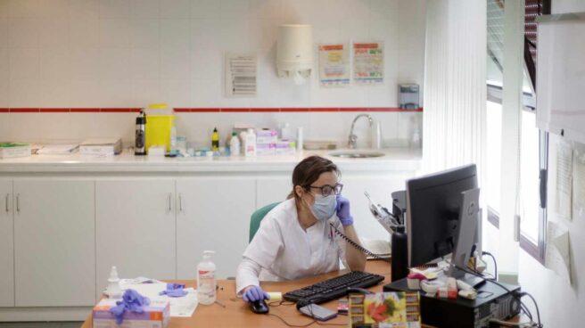 Una médica atendiendo por teléfono una consulta.