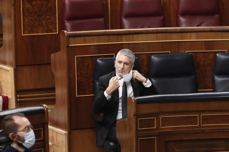 El ministro Grande-Marlaska, retirándose la mascarillas este miércoles en su escaño del Congreso de los Diputados.