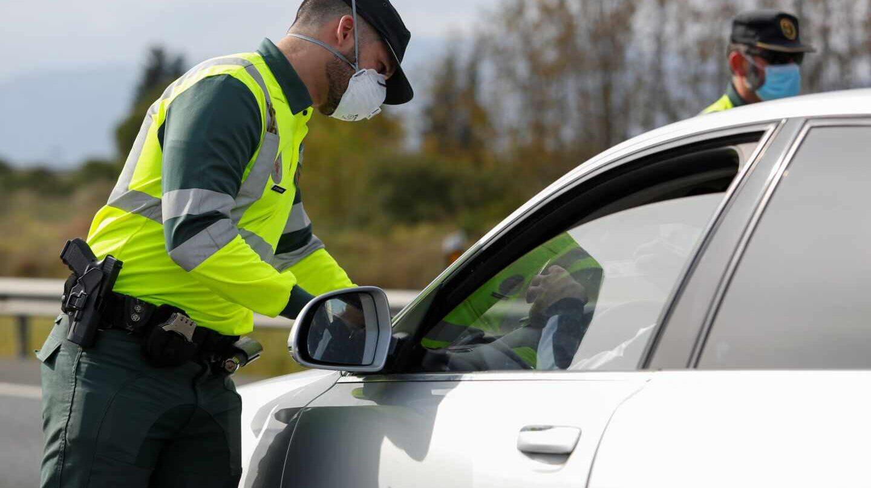 Un guardia civil, protegido con una mascarilla, durante un control de tráfico durante el estado de alarma.
