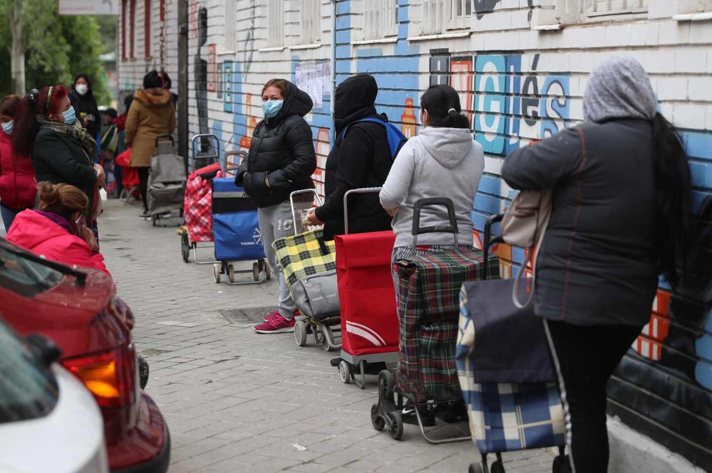 Colas para recoger comida repartida por la Asociación de Vecinos de Aluche, en Madrid.