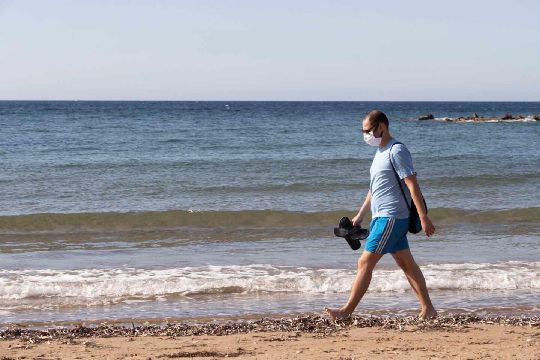 Un bañista con mascarilla en la playa de Mazarrón, en Murcia.