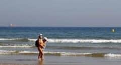 Dos bañistas con mascarilla en la playa de Gijón.