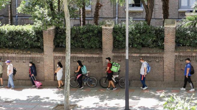 Dos riders hacen cola en Martínez Campos para conseguir una bolsa de comida