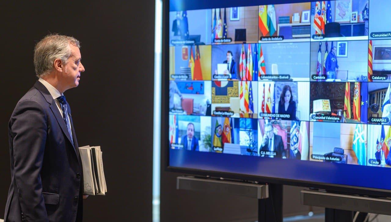 El lehendakari Iñigo Urkullu observa la pantalla con la imagen de todos los presidentes y presidentas autonómicos.