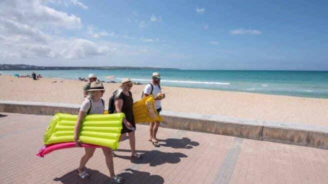 Turistas caminan por el paseo de la playa en Palma de Mallorca.