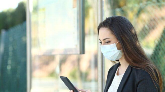 Una usuario utiliza su móvil en la calle con mascarilla.