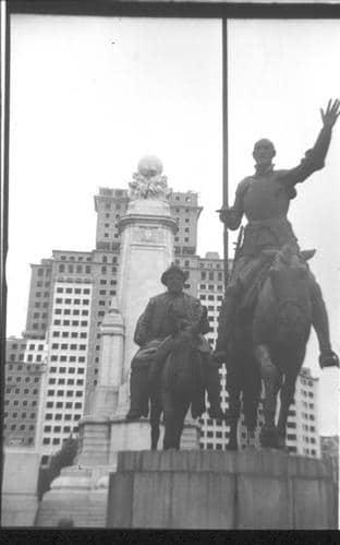 Fotografía de las estatuas del Quijote y Sancho Panza en la Plaza de España con el Edificio España detrás