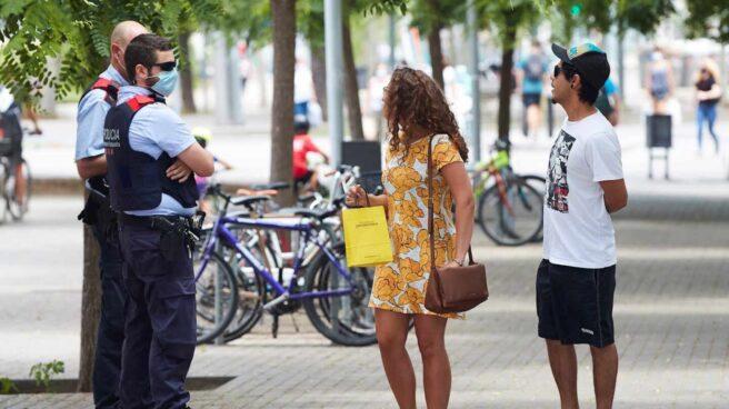 Unos agentes de los Mossos d'Esquadra informan a una pareja del uso obligatorio de la mascarilla, en Barcelona.