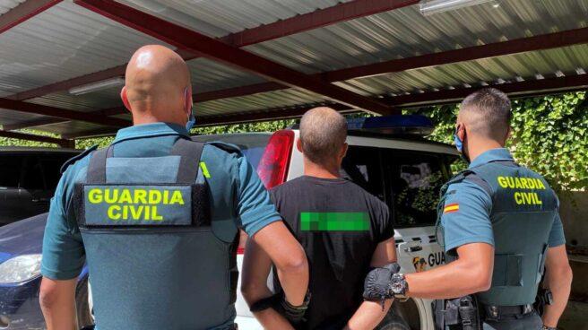 Una pareja de guardias civiles, provistos de chalecos antibala externos, conduciendo a un detenido.