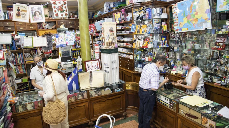 Fernanda (izquierda) y Ana (derecha) atienden a varios clientes en el mostrador de la papelería