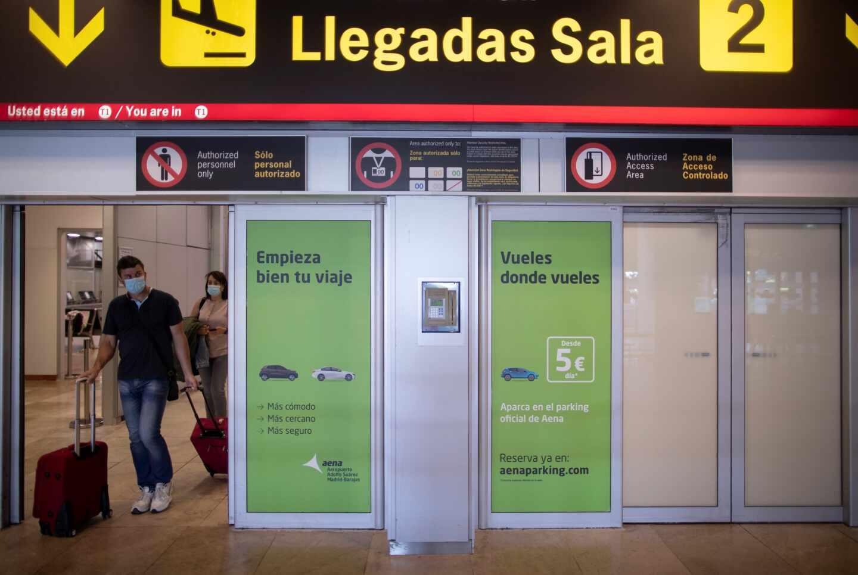 Pasajeros con mascarillas llegan al aeropuerto de Madrid-Barajas.
