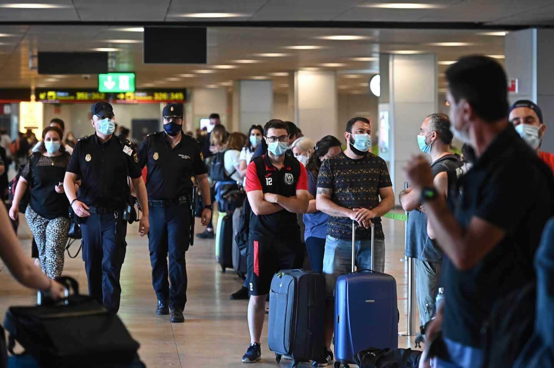 Policías en la T-1 del aeropuerto de Barajas junto a una hilera de pasajeros.