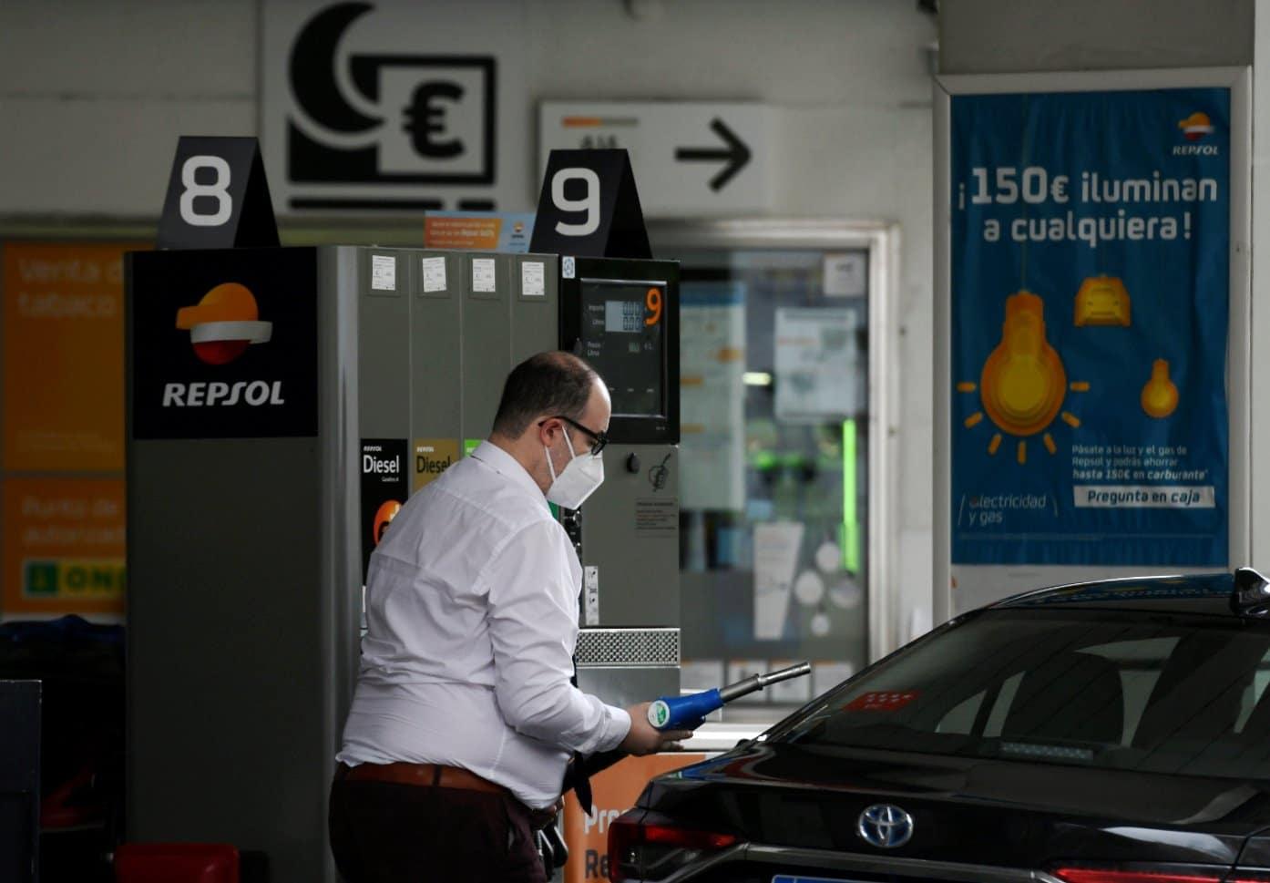 Un conductor reposta con mascarilla en una gasolinera.