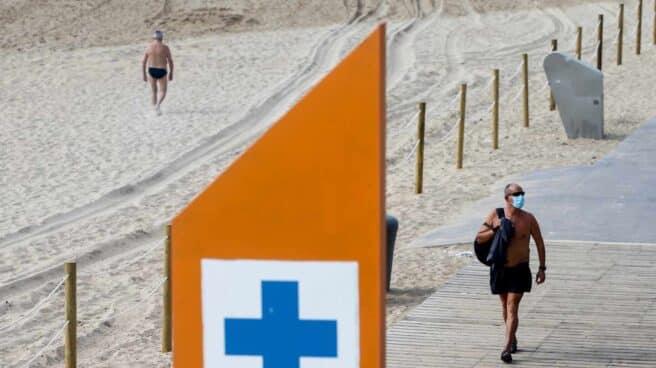 Un bañista con mascarilla en la playa de la Barcelona, en Barcelona.