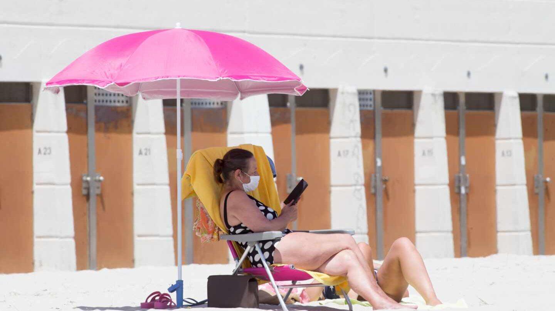 Una bañista con mascarilla en una playa de Galicia.