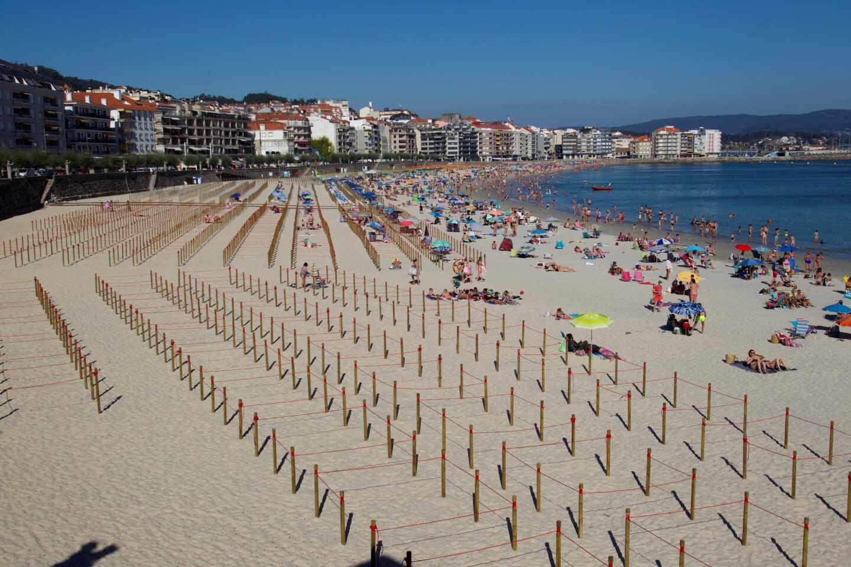 La playa de Sanxenxo (Pontevedra) con parcelas para bañistas.