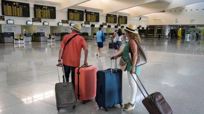 Varios turistas comprueban sus vuelos en un aeropuerto español