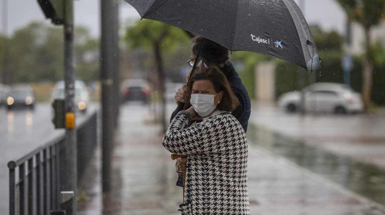 Dos personas sujetan un paraguas durante una tormenta.