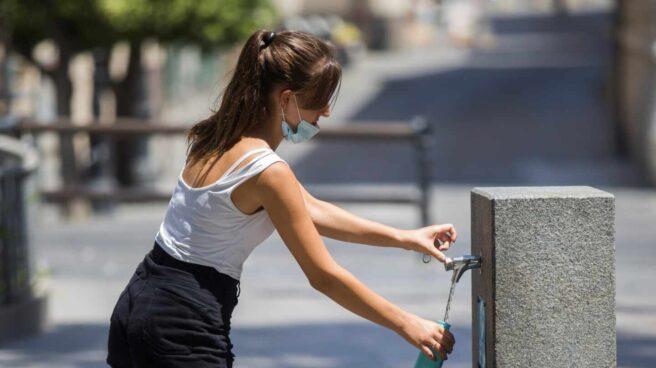 Una mujer llena una botella de agua de una fuente pública durante la ola de calor.