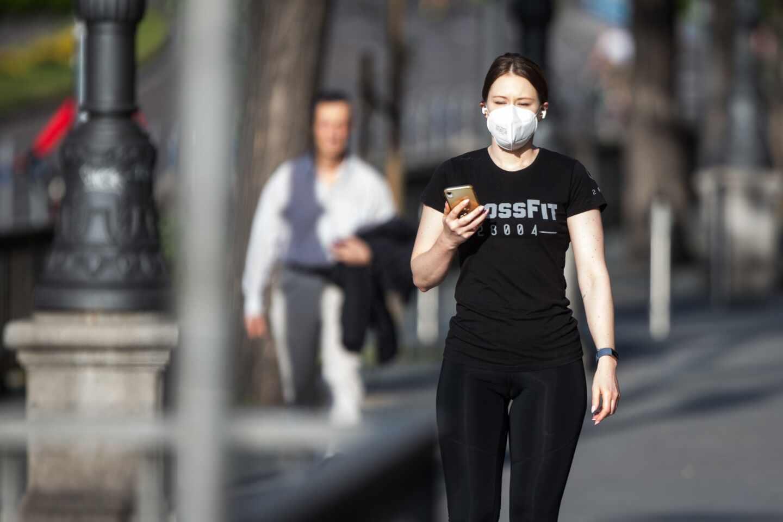 Una viandante con mascarilla utiliza su teléfono móvil.