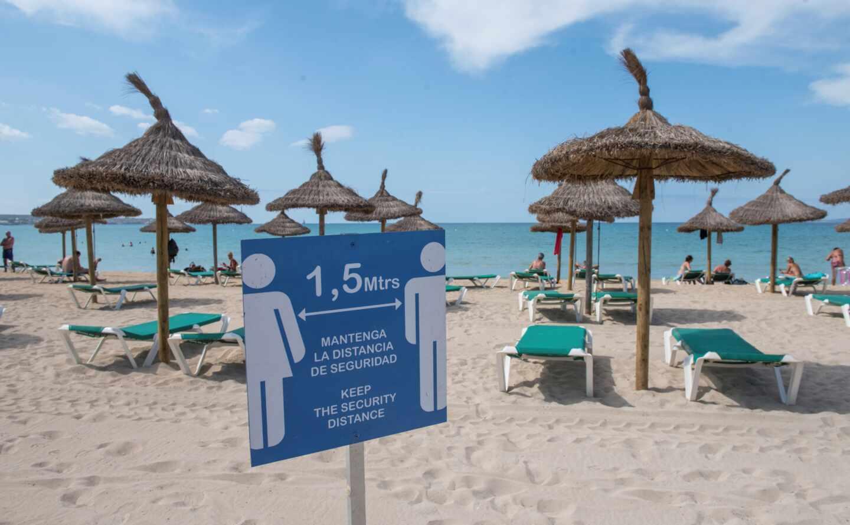 Cartel informativo sobre la distancia de seguridad en una playa de Mallorca.