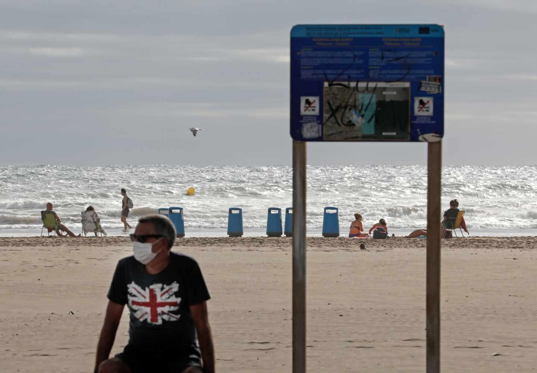Bañista con mascarilla en la playa de la Malvarrosa de Valencia.