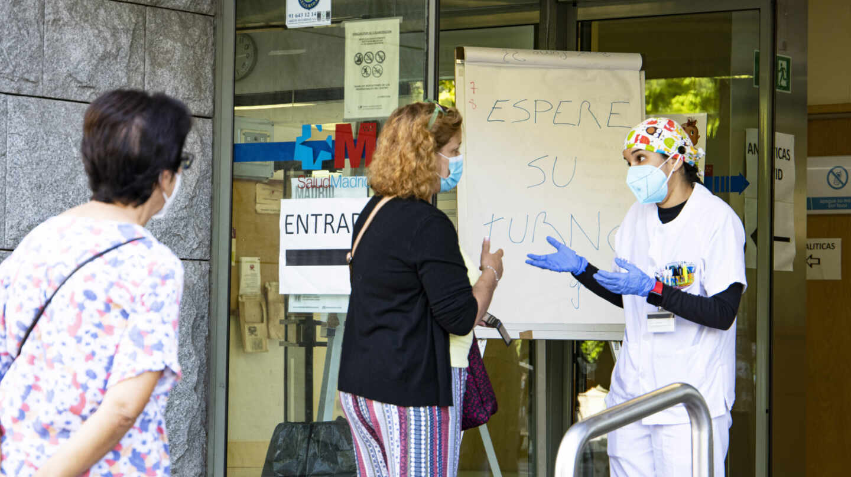 Una trabajadora del centro de salud de Doctor Cirajas atiende a una señora en la puerta