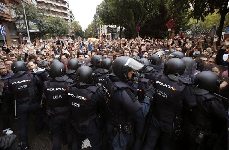 Antidisturbios de la Policía Nacional forman un cordón de seguridad en los alrededores de un colegio electoral de Barcelona el pasado 1-O.