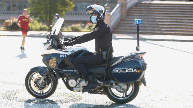 Un policía, de patrulla en motocicleta por la Plaza de España de Sevilla.
