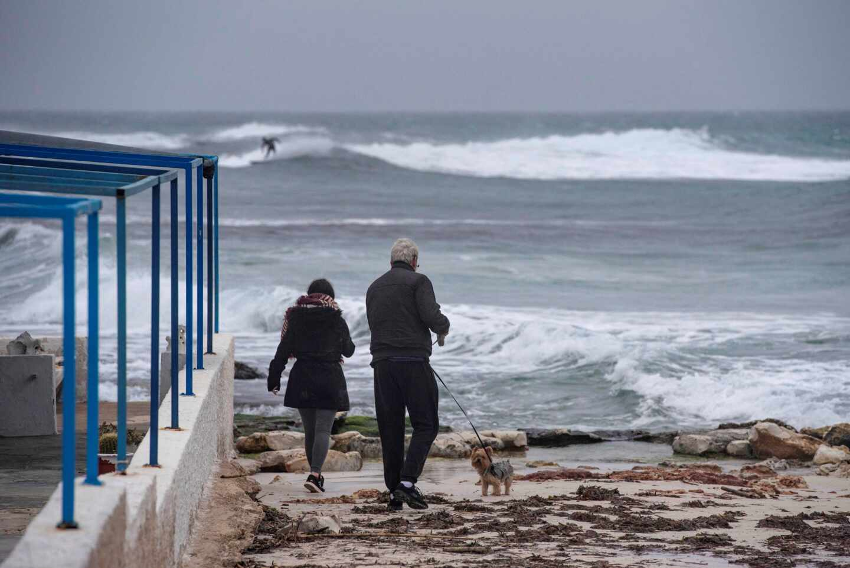 Dos personas caminan a la orilla de la costa de Biniancolla, en la isla de Menorca.
