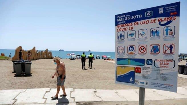 Un bañista con mascarilla en la playa de Málaga.