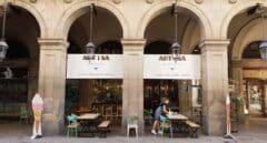una mujer recoge la mesa de un restaurante en Barcelona