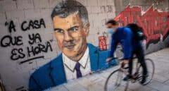 Una persona pasa frente a un mural de J.Warx, donde aparece Pedro Sánchez y una frase que éste tuiteó en 2012.