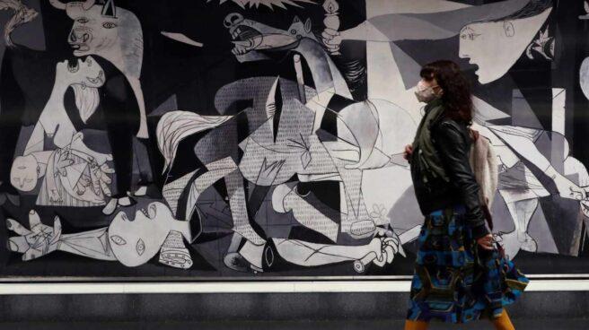 Una mujer pasa ante una reproducción del Guernica de Picasso ubicado en Atocha.