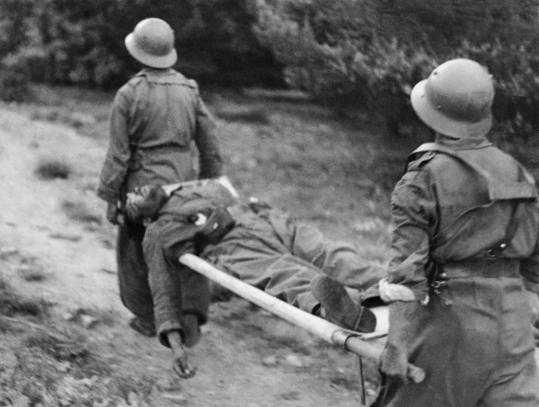 Dos hombres portan un herido foto de Gerda Taro realizada en la Guerra Civil