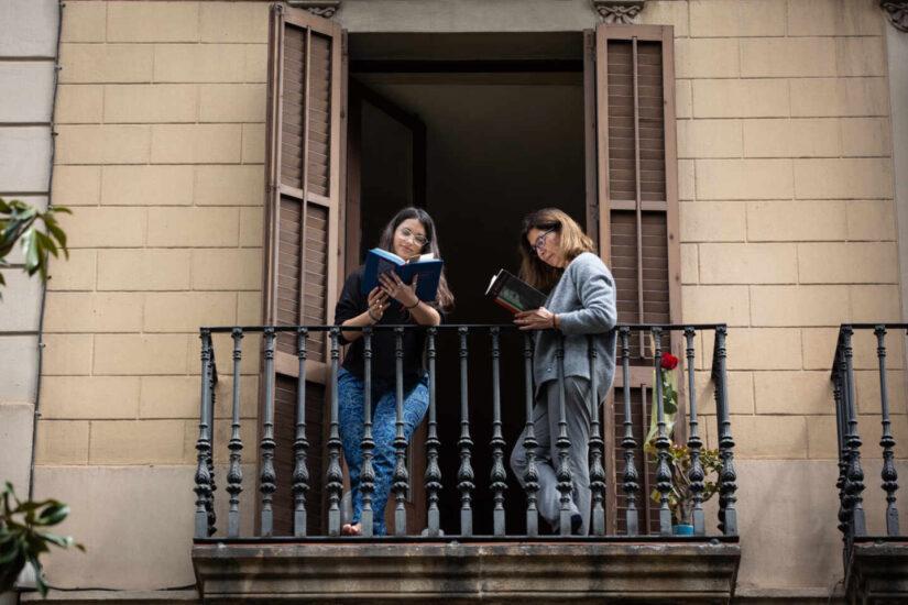 Dos jóvenes leen en el balcón de su casa