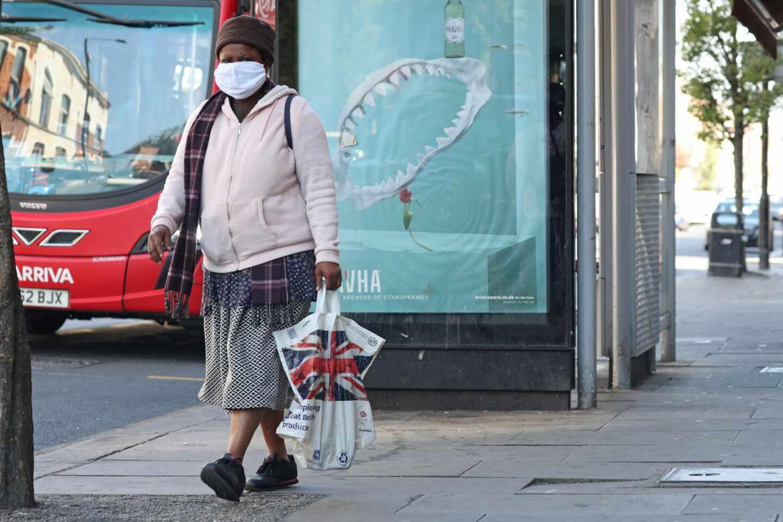 Una mujer con mascarilla camina por una calle de Londres.