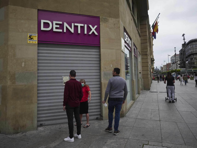 Una mujer se apoya en la puerta de una clínica Dentix, en una foto de archivo.