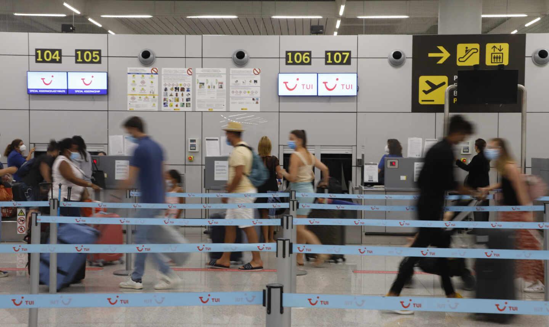 Varios pasajeros hacen cola en los mostradores de facturación de Tui en el aeropuerto de Palma de Mallorca, en una imagen de archivo.