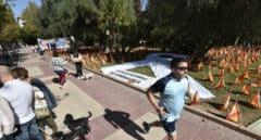 Varias personas pasean junto a las banderas de España en el Parque Isidoro Medina, en Murcia.