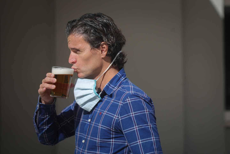 Un hombre bebe una cerveza en Sevilla.