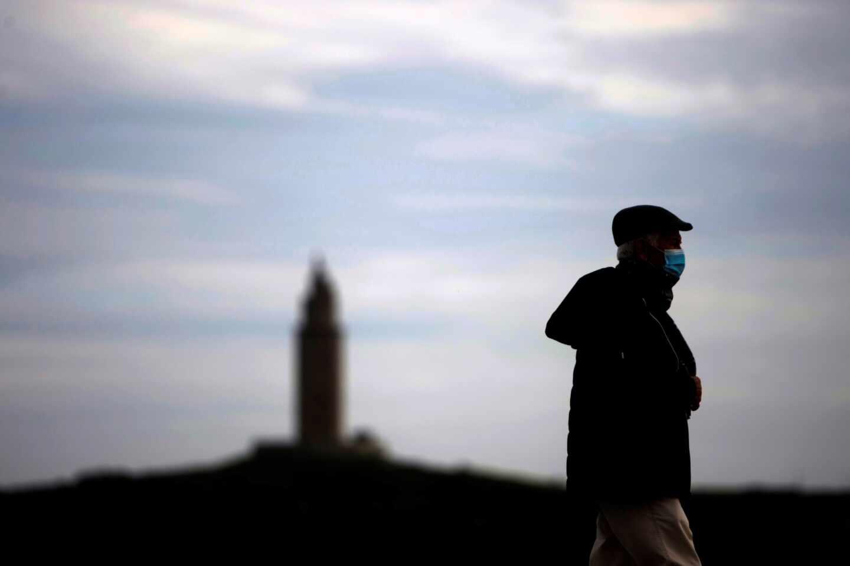 Un hombre camina por el paseo marítimo de A Coruña, con la Torre de Hércules al fondo.