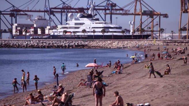 Numerosas personas disfrutan del buen tiempo en la playa de la Malagueta en Málaga.