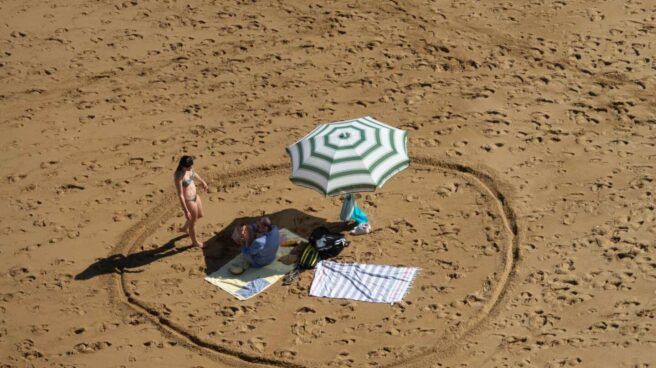 Un bañista marca la distancia de seguridad en la playa de Gijón.